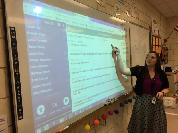 """Math teacher Heather Kohn prompts a discussion of algebraic functions using the new """"Classroom Conversation Toolset."""" It allows Kohn to use a class-wide pause feature, then project student answers to a tricky problem, but only after using the app's """"anonymizer"""" to swap student names with those of famous mathematicians. Photo: Chris Berdik"""